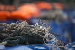 Corde de pêcheur sur les barils en plastique avec les gilets de sauvetage oranges à l'arrière-plan Photographie stock
