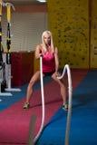 Corde di combattimento della donna di forma fisica all'esercizio di allenamento della palestra Fotografia Stock