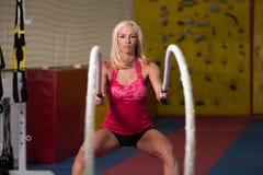 Corde di combattimento della giovane donna all'esercizio di allenamento della palestra Fotografie Stock