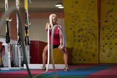 Corde di combattimento della giovane donna all'esercizio di allenamento della palestra Fotografia Stock Libera da Diritti