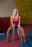 Corde di combattimento della giovane donna all'esercizio di allenamento della palestra Immagini Stock