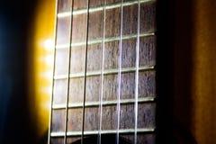 Corde di nylon sulla chitarra acustica di un musicista, alto vicino di macro immagini stock