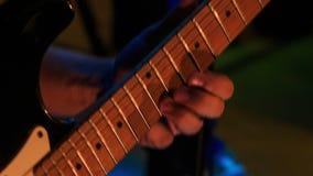 Corde di Touches Electric Guitar del chitarrista del primo piano nella notte Antivari video d archivio