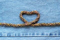 Corde en forme de coeur d'amour sur le fond de jeans de denim Photographie stock libre de droits