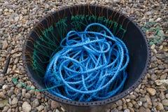 Corde en nylon bleue, poubelle noire, plage pebbled Photos libres de droits