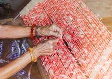 Corde en plastique attachée dans le fil par des mains de dames âgées, vieux sil folklorique de manière Photos libres de droits