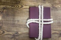 Corde enroulée autour d'un livre sur la table en bois Photographie stock