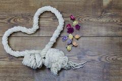 Corde et fleurs en forme de coeur sur le bois Décor de jour du ` s de Valentine Photographie stock libre de droits