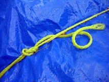 Corde jaune sur la bâche de protection bleue Photographie stock libre de droits