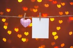 Corde naturelle des coeurs de Valentine d'amour de guingan et agrafes en bois accrochant sur le fond d'étincelle de bokeh de coeu Photographie stock libre de droits