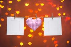 Corde naturelle des coeurs de Valentine d'amour de guingan et agrafes en bois accrochant sur le fond d'étincelle de bokeh de coeu Photos libres de droits
