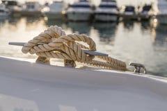 Corde nautique en gros plan de noeud attachée autour de l'enjeu sur le bateau ou le bateau, corde d'amarrage de bateau Images libres de droits