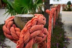 Corde nautique orange sur les poteaux en bois Photos libres de droits
