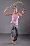 Corde à sauter de jeune adolescente musculaire en bonne santé dans le studio Enfant s'exerçant avec sauter sur le fond gris Image libre de droits