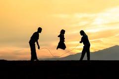 Corde silhouettée d'enfants sautant dans le coucher du soleil Photographie stock libre de droits