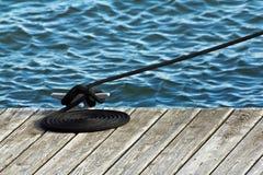 Corde soigné enroulée sur le dock de bateau Photos stock