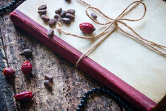 Corded book with beads, dogrose, nuts Stock Photography