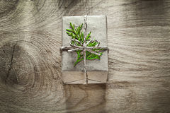 Corded handmade gift box with thuya branch on wooden board Stock Photo