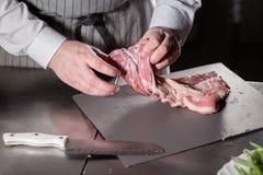 Corderos raros listos para el adobo con romero El cocinar con el fuego en sartén Cocinero profesional en una cocina de Imagenes de archivo