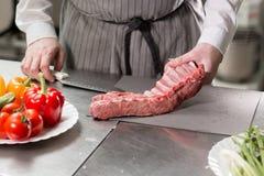Corderos raros listos para el adobo con romero El cocinar con el fuego en sartén Cocinero profesional en una cocina de Fotografía de archivo