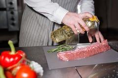 Corderos raros listos para el adobo con romero El cocinar con el fuego en sartén Cocinero profesional en una cocina de Foto de archivo libre de regalías
