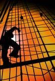 CORDES S'ÉLEVANTES DE BATEAU DE SILHOUETTE D'HOMME DE MARIN CONTRE LE CIEL DE COUCHER DU SOLEIL D'OR Photo libre de droits
