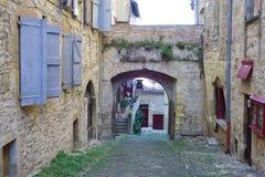 Cordes-sur-Ciel Tyst gränd och borggård mellan hus som fästas till stadsväggen royaltyfri fotografi