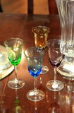 Cordial glasses and carafe on table Royalty Free Stock Photos