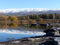A cordilheira coberto de neve refletiu no lago na represa do carniceiro, Otago central, Nova Zelândia Fotos de Stock Royalty Free