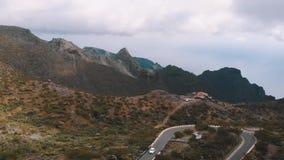 Cordillera en el parque nacional en tiempo nublado, el camino en el top y los coches, aéreos almacen de metraje de vídeo