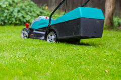 Cordless battery power lawn mower close up on green grass backgr Stock Images