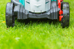 Cordless battery power lawn mower close up on green grass backgr Royalty Free Stock Photography