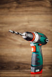 Cordless drill against wooden background Royalty Free Stock Photo
