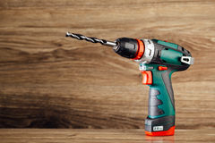 Cordless drill against wooden background Royalty Free Stock Images