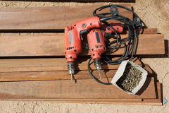 Cordless drill and large screws on a wood Stock Photos