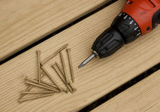 Cordless drill and screws. Cordless drill and large screws on a wood background Royalty Free Stock Photo