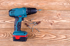 Cordless drill. With screws on a wooden background Royalty Free Stock Photos