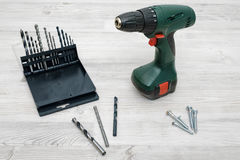 A cordless drill set to stand on a wooden table background with a set of bits in the box Stock Images