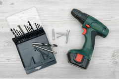 A cordless drill set to stand on a wooden table background with a set of bits in the box Royalty Free Stock Photos
