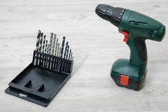 A cordless drill set to stand on a wooden table background with a set of bits in the box Royalty Free Stock Photo