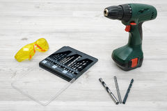 A cordless drill set to stand on a wooden table background with a set of bits in the box and yellow protective glasses Royalty Free Stock Images