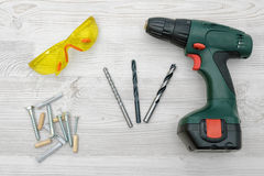 A cordless drill set on a wooden table background with a set of bits in the box and yellow protective glasses around. Royalty Free Stock Image