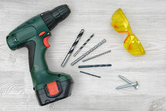 A cordless drill set on a wooden table background with a set of bits in the box and yellow protective glasses around. Royalty Free Stock Photos