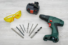 A cordless drill set on a wooden table background with a set of bits in the box and yellow protective glasses around. Stock Images
