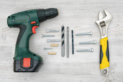 A cordless drill, a wrench, several drill bits, screw bolts and dowels on light wood background. Tools and equipment. Hardware store. Hand-made and renovation Stock Images
