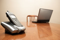 Cordless phone and laptop on table Stock Image