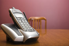 Cordless phone on a table with chair. A cordless phone on a table with an out of focus chair Stock Photos