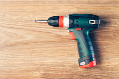 Cordless screwdriver against wooden background Royalty Free Stock Photography