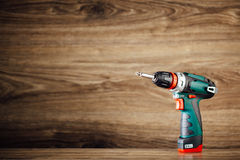 Cordless screwdriver against wooden background Royalty Free Stock Photos