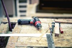 Cordless screwdriver and carpenter tools in wood industrial fact. Ory stock photography